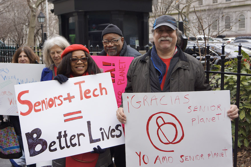 Senior Planet members hold up signs outside City Hall